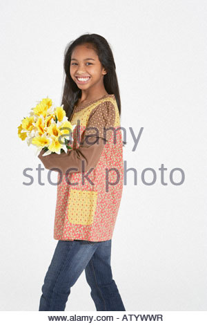 Young girl indoors holding bouquet of flowers - Stock Photo
