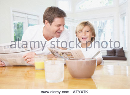 Man and young boy in kitchen reading newspaper and laughing - Stock Photo