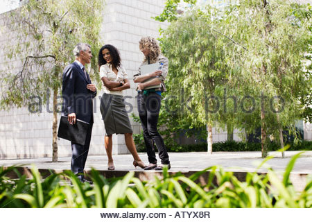Three businesspeople outdoors on sidewalk talking - Stock Photo