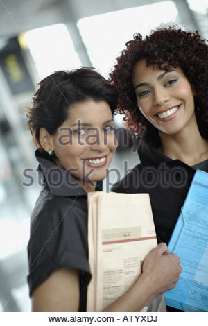 Two businesswomen in office with paperwork - Stock Photo