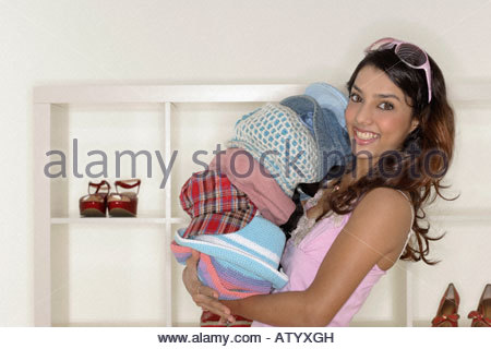 Woman in department store carrying pile of hats - Stock Photo
