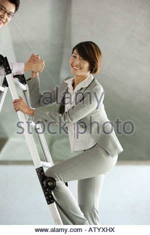 Businessman helping businesswoman up ladder in structure - Stock Photo