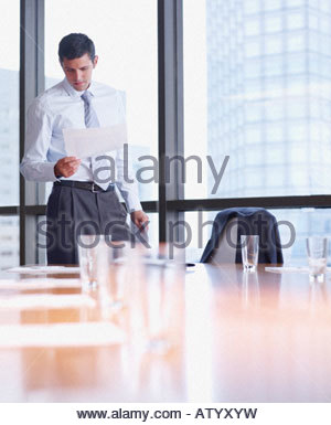 Businessman in boardroom with paperwork by large windows - Stock Photo