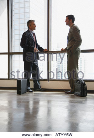 Two businessmen in corridor by large windows - Stock Photo
