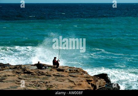 Fisherman on the rocks at Praia da Luz Algarve Portugal - Stock Photo