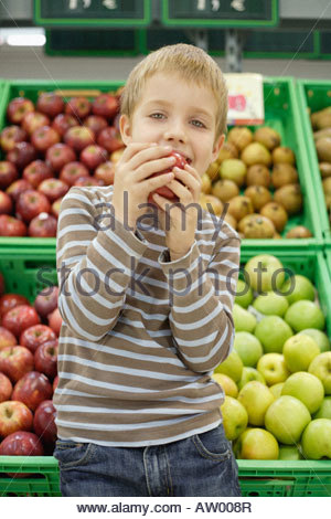 Young boy in grocery store eating apple - Stock Photo