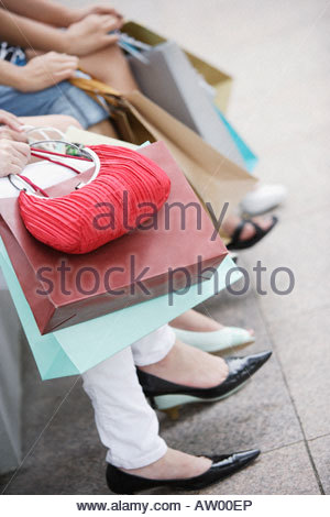Three women outdoors with shopping bags - Stock Photo