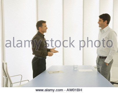 Two businessmen in a boardroom talking - Stock Photo