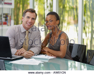Two businesspeople in an office with a laptop - Stock Photo