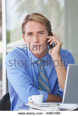 Businessman at outdoor patio table on his mobile phone sitting with laptop - Stock Photo