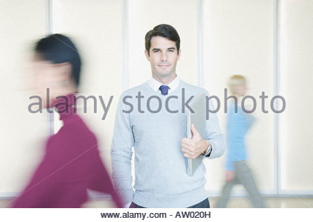 Businessman in office holding laptop with co-workers going by - Stock Photo