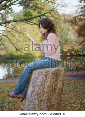 Woman sitting with book outdoors by a lake on a stump - Stock Photo
