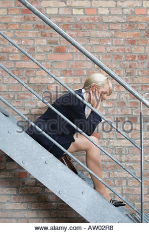 Businesswoman sitting on stairs - Stock Photo