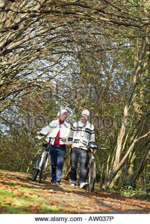 Couple outdoors walking with bicycles on a path in a park - Stock Photo