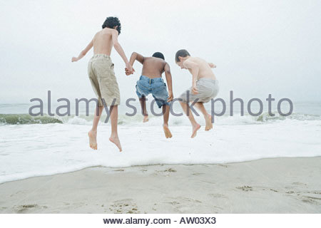 Boys jumping in the sea - Stock Photo
