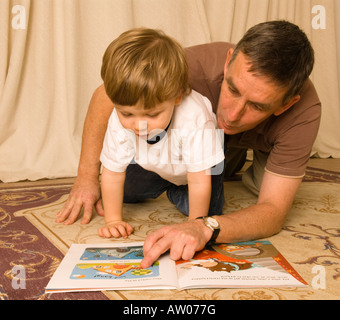 grandfather father reading on floor with son grandson two years old - Stock Photo