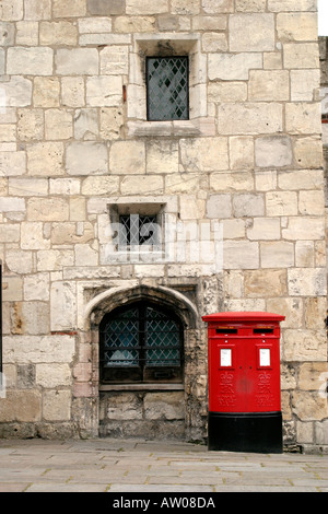 Red post box standing at side of ancient window with diamond leaded lights and medieval masonry - Stock Photo