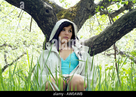 young woman sitting in grass leaning against tree - Stock Photo