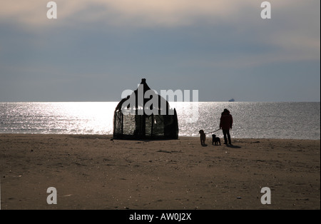 man in distance walking dogs on deserted beach with domed bamboo hut - Stock Photo