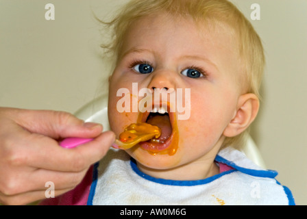 Horizontal close up of a pretty Caucasian baby girl in a high chair at dinner time with food all over her face - Stock Photo