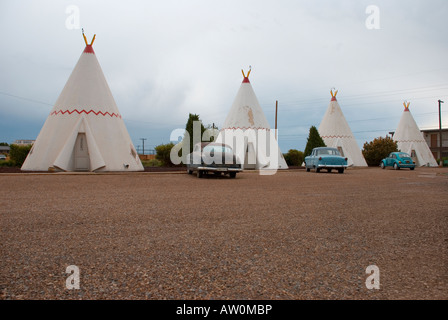 Old Route 66 motel with rooms in the shape of teepees and vintage cars parked in front, USA - Stock Photo