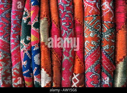Stack of everyday and ceremonial hand embroidered silk and woven fabrics from Pakistan - Stock Photo