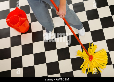 Woman standing with mop beside red bucket Closeup on woman s legs and mop High angle view White background - Stock Photo