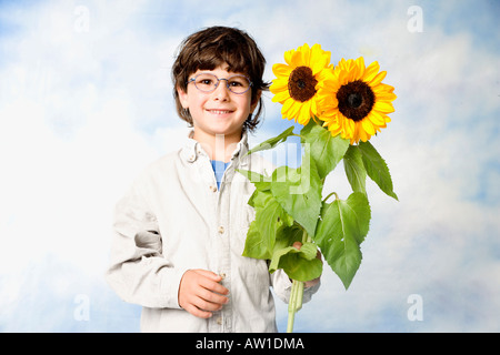 Young boy smiling into camera with sunflowers in his hand - Stock Photo