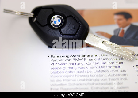 Car key on an insurance policy - Stock Photo