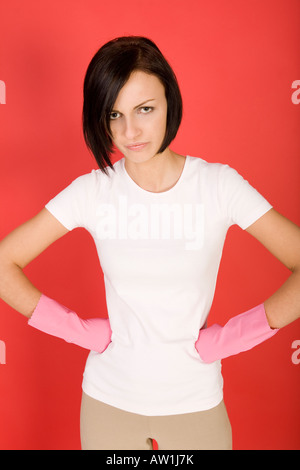 Young woman in pink rubber gloves with hands on hips She s looks like angry Looking at camera front view - Stock Photo