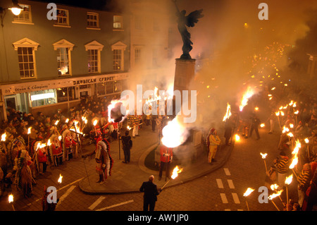 Sparks and flames fly around the war memorial at the heart of the annual spectacle of Lewes Bonfire night celebrations - Stock Photo