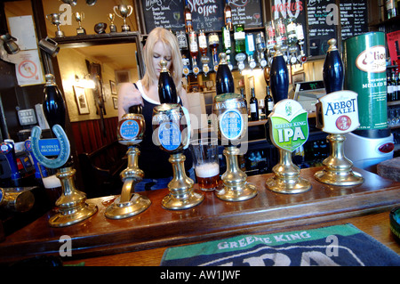 A barmaid pours a pint of the local Harveys of Lewes ale at the Lewes Arms pub in  Lewes Sussex owned by brewers - Stock Photo
