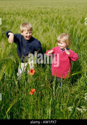 Children playing in grain field - Stock Photo