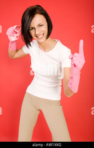 Young woman in pink rubber gloves holding in hand washcloth and threateningly finger She s looks like very angry - Stock Photo
