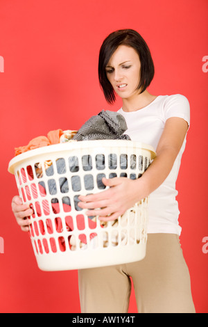 Young woman standing with full laundry basket She s looks like angry Front view - Stock Photo