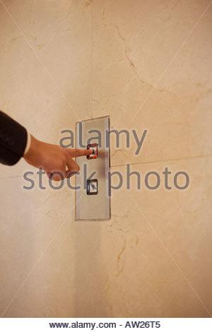 Man pressing elevator button - Stock Photo
