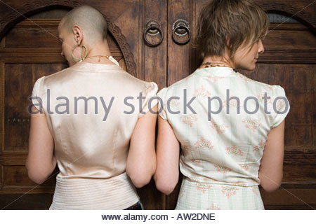 Twin sisters standing against a door - Stock Photo
