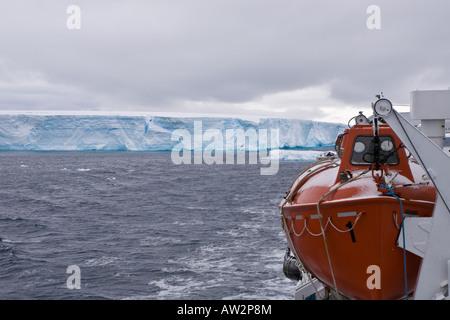 Closeup of lifeboat on ship passing huge tabular iceberg in background - Stock Photo