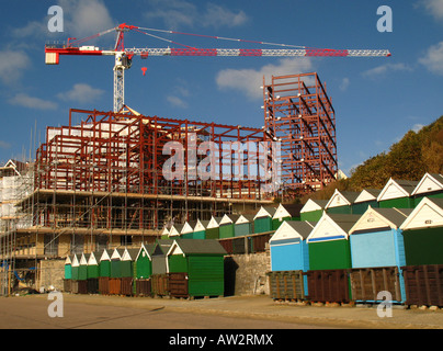 Crane and construction work towering over the beach huts at Boscombe's Honeycombe Chine, near Bournemouth, Britain. - Stock Photo