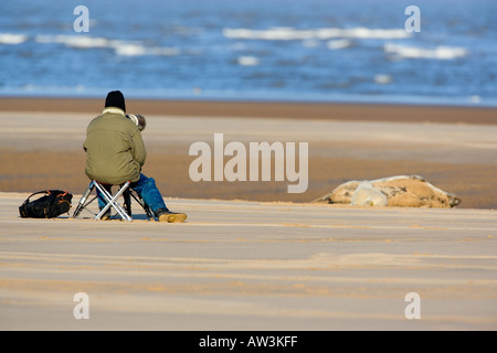 A Man On The Beach With A Fold Up Chair And Push Bike And