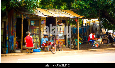 Cycle repair shop, Mauritius.  Workers look on whilst boss or customer reads paper? - Stock Photo