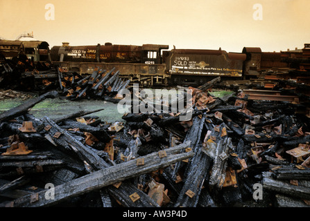 Rusting steam train and burned sleepers in scrap yard Barry Wales UK - Stock Photo