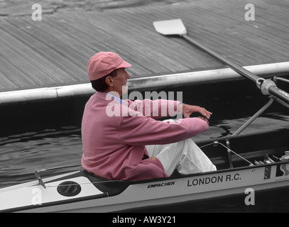 Mono and pink manipulated image: Cox of the Leander Club sitting in stern of rowing boat at Henley Royal Regatta, - Stock Photo