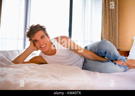 Young man smiles lays on bed. - Stock Photo