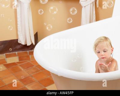 Little girl taking a bath bubbles. - Stock Photo