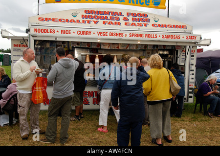 people queueing for food at an oriental nooles fast food mobile catering unit or caravan at an outdoor event - Stock Photo