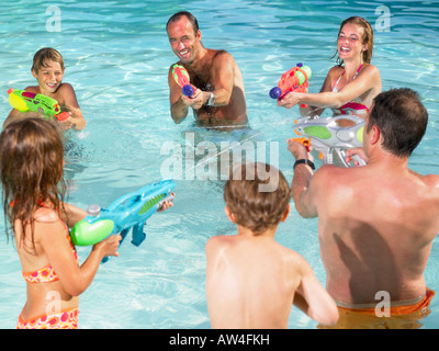 Kids and adults playing with water guns. - Stock Photo
