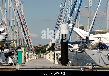 a jetty pontoon in a modern yacht marina showing the jetties with expensive yachts and boats moored and tied up - Stock Photo