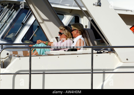 a woman and man lady and gentleman sat on a luxury motor yacht in the sunshine wearing sunglasses and relaxing during - Stock Photo