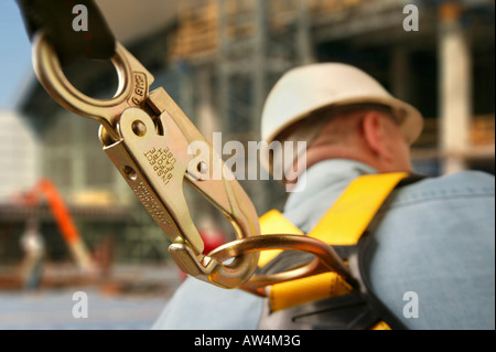 Detail of the clip on a safety harness of a construction worker. - Stock Photo